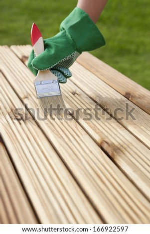 Hand with brush on a wooden background  - stock photo