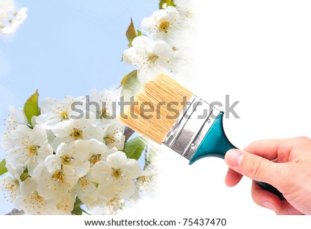 Hand with brush painting natural image with flowers - stock photo
