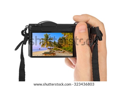 Hand with camera and Maldives beach photo (my photo) isolated on white background - stock photo