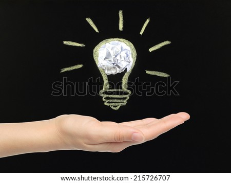 Hand with chalk light bulb with crumpled paper drawn on blackboard by hand not in photoshop - stock photo