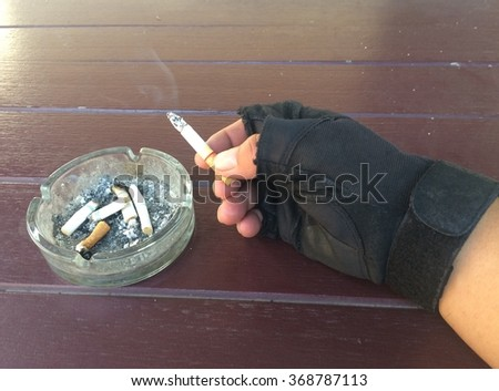 hand with cigarette butt and portrait of a child in ashtray. - stock photo
