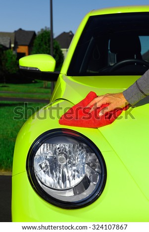 Hand with cloth washing a car. Waxing and polishing. - stock photo