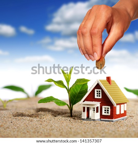 Hand with coin and house over sky background. - stock photo