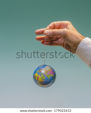 hand with dangling globe Africa, Europe, Asia, Russia prominent - stock photo
