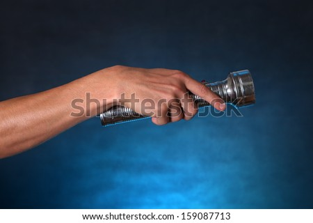 Hand with Flashlight on the dark background - stock photo