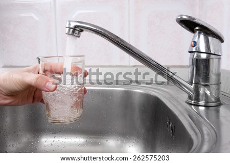 Hand with glass of water poured from kitchen faucet  - stock photo