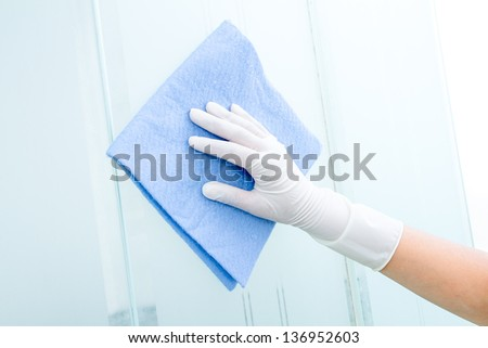 Hand with glove and blue sponge cleaning the bathroom glass - stock photo