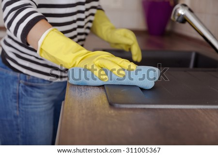 Hand with glove using cleaning  Kitchen at home. - stock photo