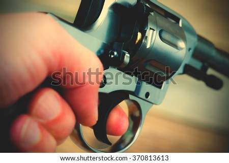 hand with gun, close-up. instagram image filter retro style - stock photo