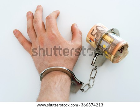Hand with handcuffs and money. Bribery concept. - stock photo