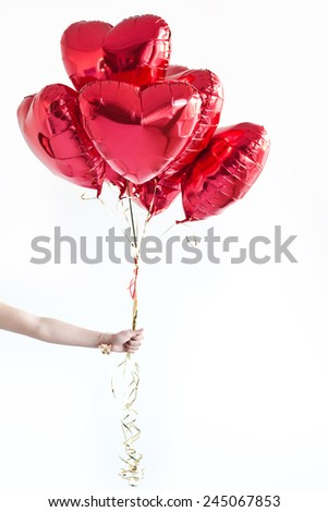 Hand with heart-shaped balloons. Valentine's day. - stock photo