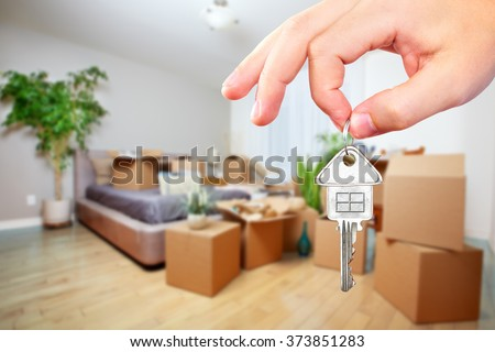 Hand with house key. - stock photo