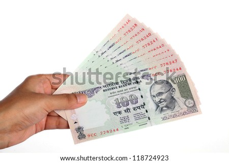 Hand with hundred Indian rupee notes on white background - stock photo