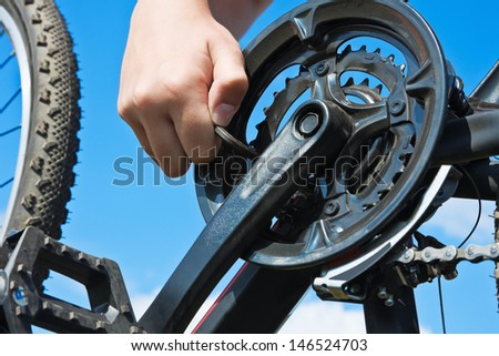 hand with key repairs bicycle against the sky - stock photo