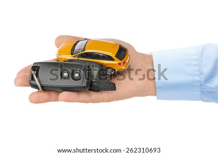 Hand with keys and car isolated on white background - stock photo