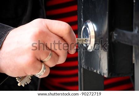 Hand with keys unlocking the front door, outdoor - stock photo