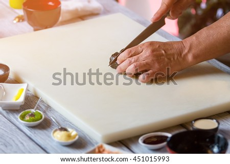 Hand with knife cutting sushi. Cooking board with sushi roll. Professional's work in cafe kitchen. How to prepare tasty food. - stock photo