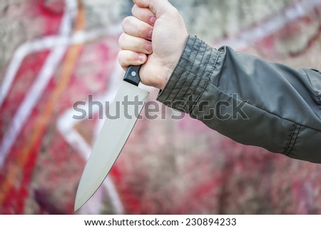 Hand with knife near old stone wall - stock photo