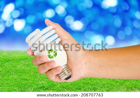Hand with lamp and sign recycle on spring background - stock photo