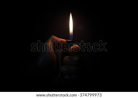 Hand with lighter igniting sparks on dark background - stock photo