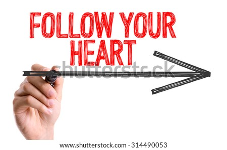 Hand with marker writing the word Follow Your Heart - stock photo