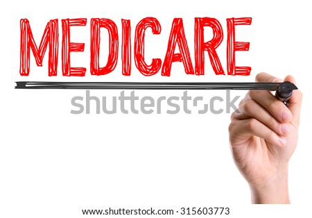 Hand with marker writing the word Medicare - stock photo