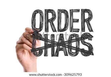 Hand with marker writing the word Order Chaos - stock photo