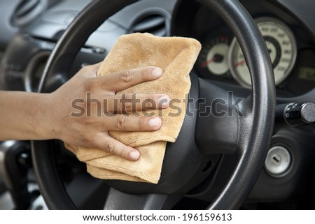 hand with microfiber cloth polishing steering wheel - stock photo