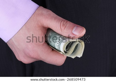 Hand with money. A man in business clothes with money in hand. A fist full of money. Dollar bills clenched in his hand. - stock photo