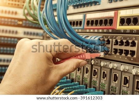 hand with network cables connected to servers in a datacenter - stock photo