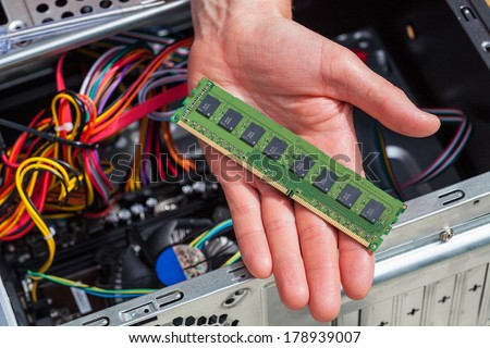 Hand with new ram data for computer - stock photo