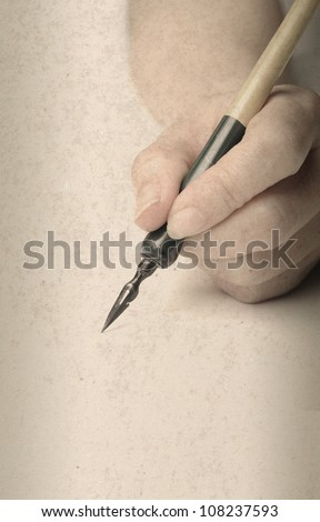 hand with old style pen - stock photo