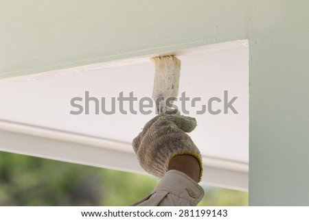 Hand with paintbrush painting on the wall outdoor - stock photo
