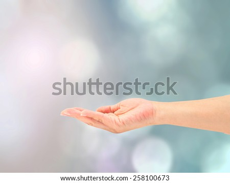 Hand with palm up isolated on blurred colorful nature background - stock photo