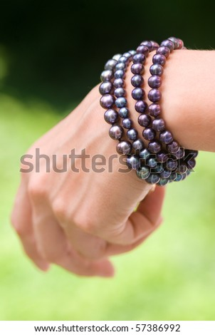 Hand with pearl bracelets - stock photo
