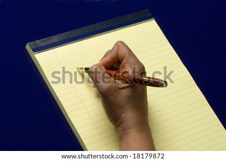 Hand with pen in it writing on yellow notepad on blue background, taking notes - stock photo