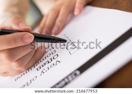 Hand with pen marking work often in the checklist - stock photo