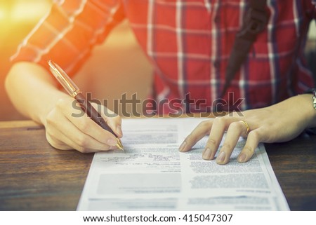 Hand with pen over application form,Businessperson Signing Contract,writing paper at the desk,man writing with pen and reading books,man Signing,Contract,Form.in office ,vintage color,selective focus. - stock photo