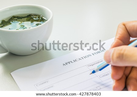 Hand with pen over application form with tea cup - stock photo