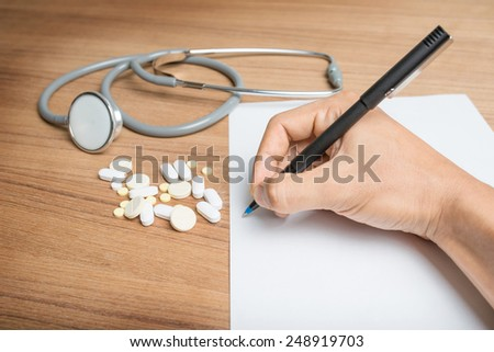 Hand with pen over blank paper form with stethoscope and pills. - stock photo