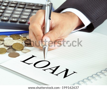 Hand with pen pointing to LOAN word on the paper - financial & business concept - stock photo