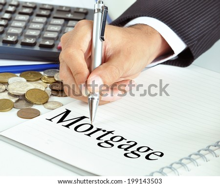 Hand with pen pointing to Mortgage word on the paper - financial & business concept - stock photo