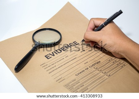 hand with pen writing on evidence paper with magnifying glass - stock photo