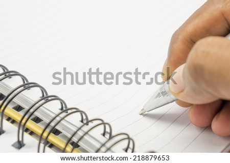 Hand with pen writing on white background - stock photo