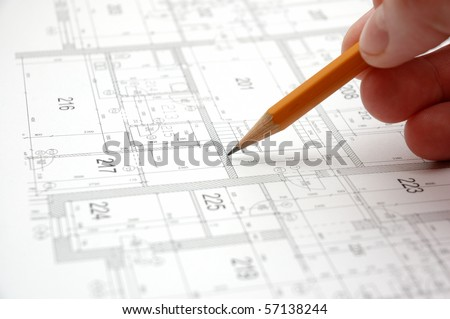 Hand with pencil on building drawing - stock photo