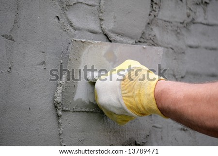 Hand with plastering tool apply plaster - stock photo