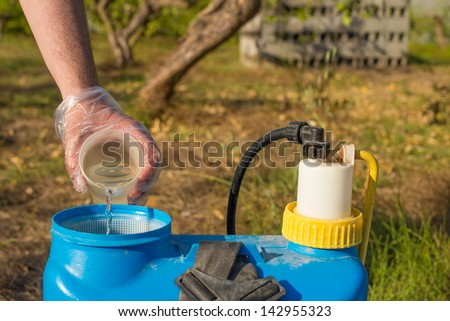 Hand with plastic glove filling pesticide into a garden sprayer - stock photo