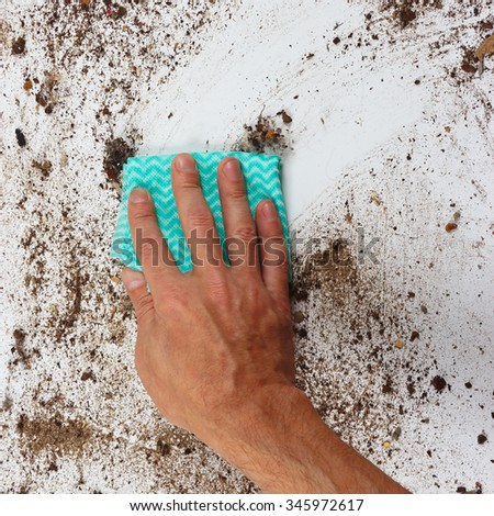 Hand with rag cleans a very dirty surface - stock photo