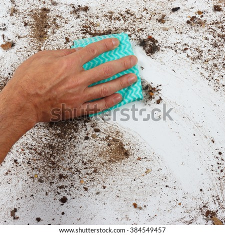 Hand with rag wiping the heavily dirty surface - stock photo