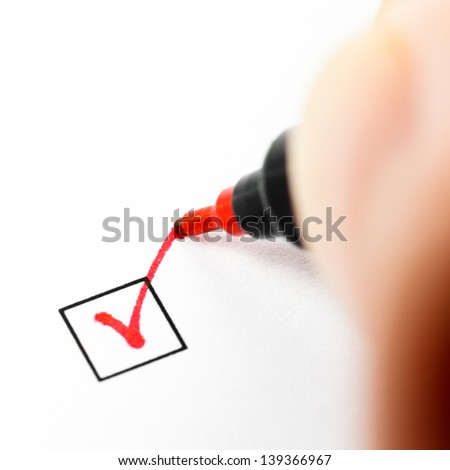 Hand with red pen marking a check box - stock photo